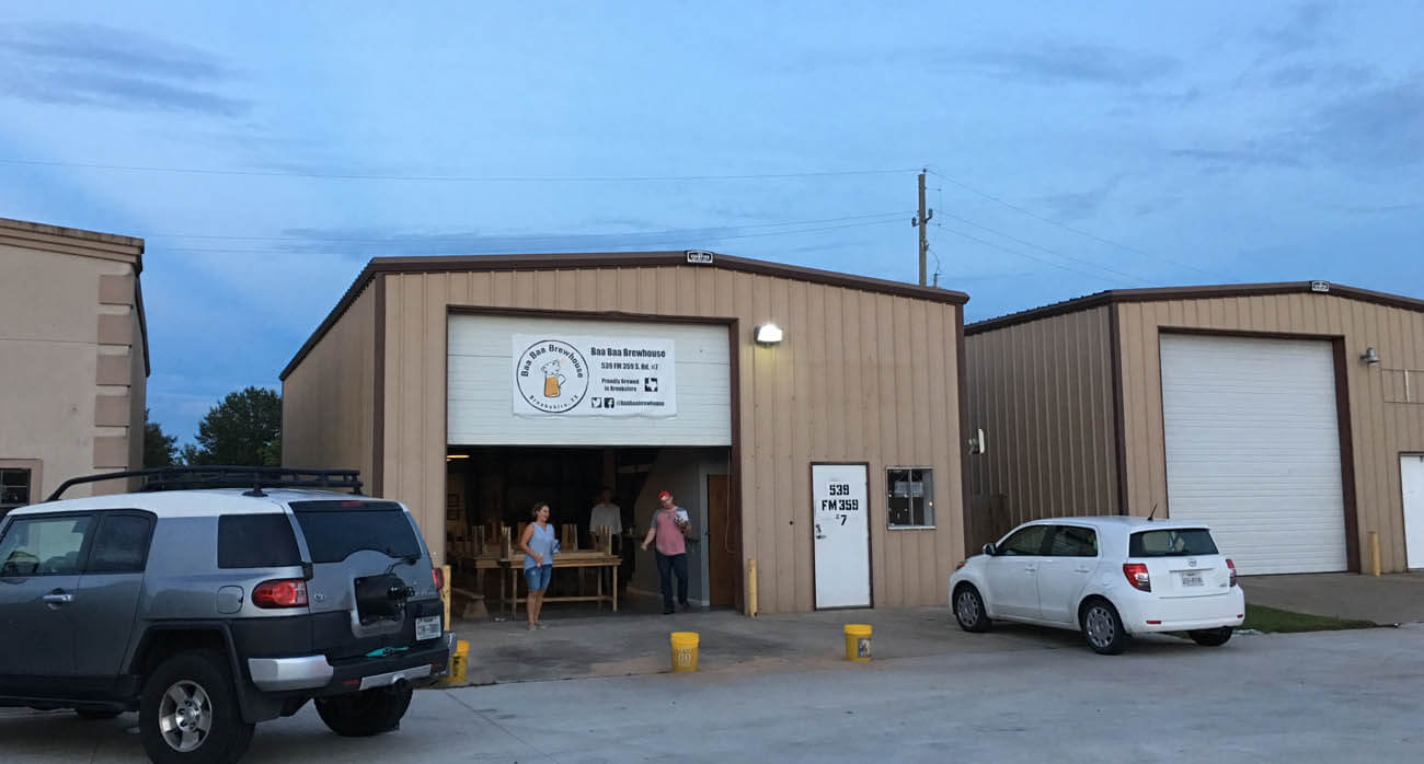 beer-chronicle-houston-craft-beer-review-featured-_0000_baa-baa-brewhouse-brookshire-parking-lot-and-brown-warehouse-buildings