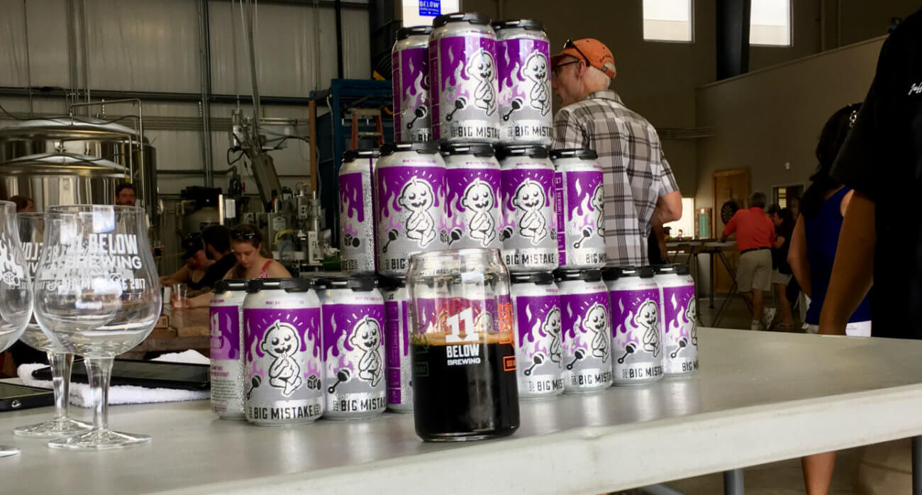 Beer-Chronicle-Houston-Craft-Beer-Review-11-Below-Big-Mistake-In-Glass-In-Front-Of-Can-Stack