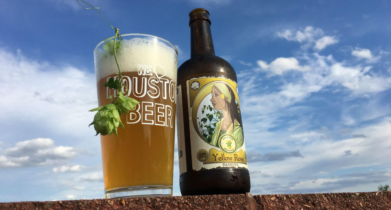 beer-chronicle-houston-craft-beer-review-lone-pint-yellow-rose-beer-in-pint-glass-with-hop-bud-hanging-out-of-glass-next-to-bottle-with-sky-background